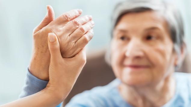 Alte Frau macht Krankengymnastik mit den Händen.