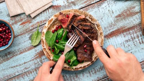 Jemand isst ein gegrilltes Rindersteak mit Salat auf einem blauen Holztisch.