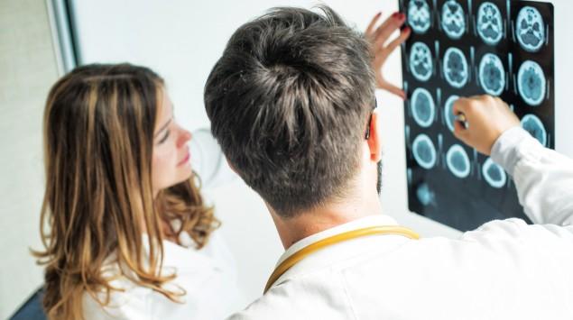 Ein Arzt und eine Ärztin schauen sich ein Röntgenbild von einem Schädel an.