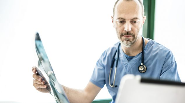 Ein Arzt hält ein Rötgenbild in der rechten Hand und blickt nachdenklich auf ein Notepad.