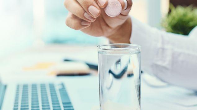 Eine Frau hält eine rosafarbene Brausetablette über ein Glas Wasser.