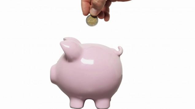 Jemand wirft eine Münze in ein rosa Sparschwein.