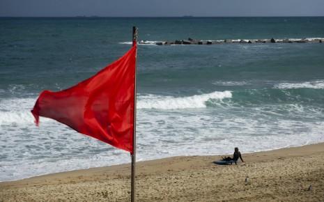 Eine rote Flagge am Meeresstrand