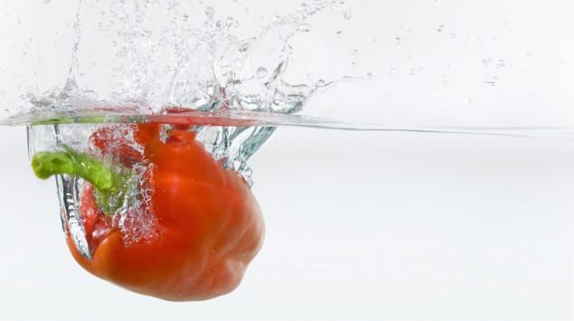 Das Bild zeigt eine rote Paprika in einem Wasserbecken.