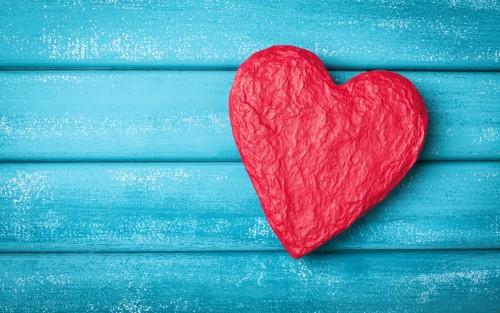 Ein rotes Herz auf blauem Holzuntergrund.