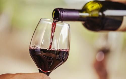 Jemand schenkt ein Glas Rotwein ein.