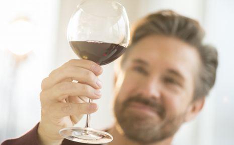Bluthochdruck senken: Ein blickt prüfend auf ein Glas Rotwein.