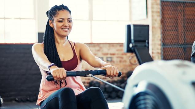 Eine Frau rudert im Fitnessstudio auf einem Rudergerät.