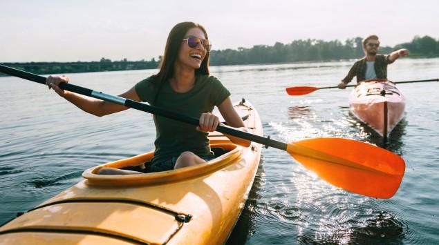 EIne junge Frau und ein junger Mann rudern auf einem See