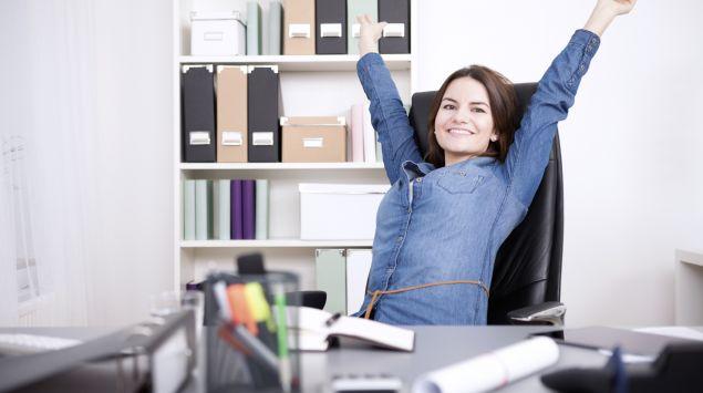 Ein Frau streckt im Büro die Arme nach oben.
