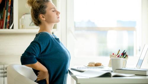 Eine Frau sitzt am Schreibtisch und stemmt die Hände in den Rücken.