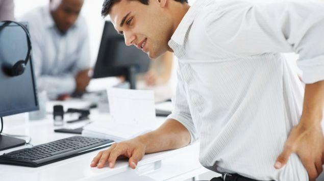 Man sieht einen Mann, der vorm Computer sitzt, und sich den Rücken hält.