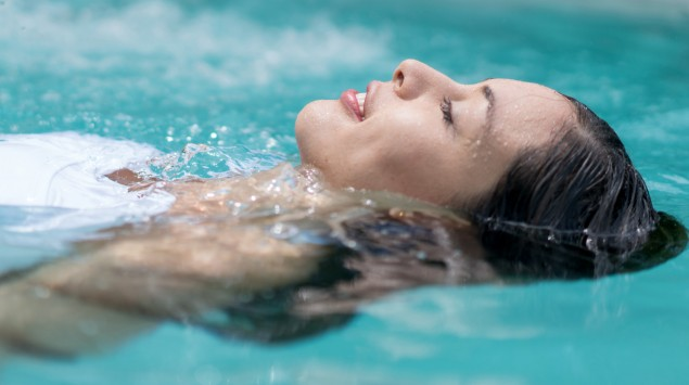Man sieht eine Frau beim Rückenschwimmen.
