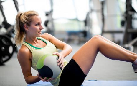 Eine Frau macht eine Fitnessübung (Russian Twist).