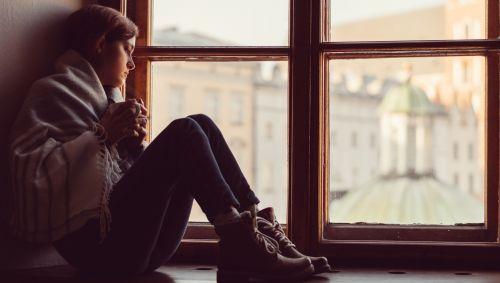 Junge Frau sitzt deprimiert in Fensternische.