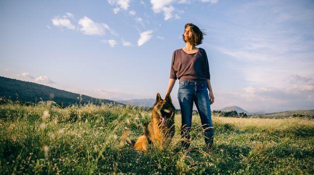 Das Bild zeigt eine Frau mit ihrem Schäferhund auf einer Wiese