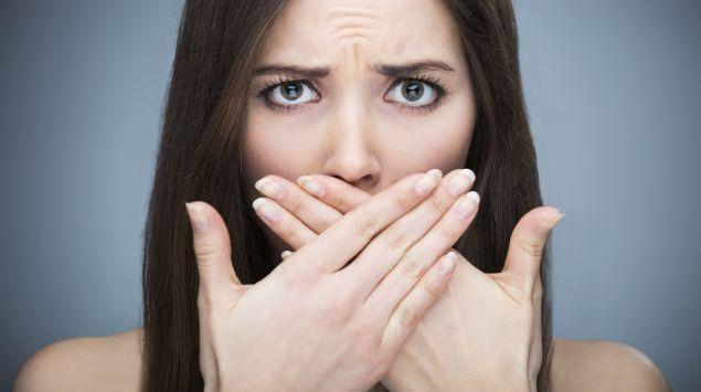 Frau bedeckt ihren Mund mit ihren Händen und schaut bestürzt