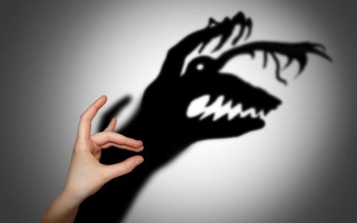 Jemand wirft mit der Hand einen Schatten an die Wand, der Schatten bildet jedoch eine monsterartige Figur ab.