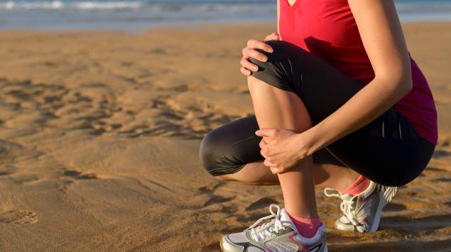 Eine Joggerin kniet am Strand und hält ihr schmerzendes Schienbein.