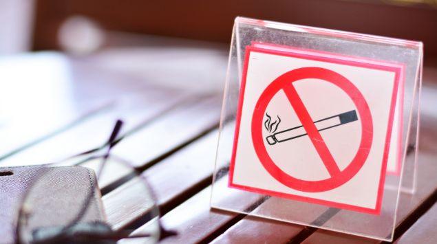 Ein Schild mit einer durchgestrichenen Zigarette, das auf einem Tisch steht.
