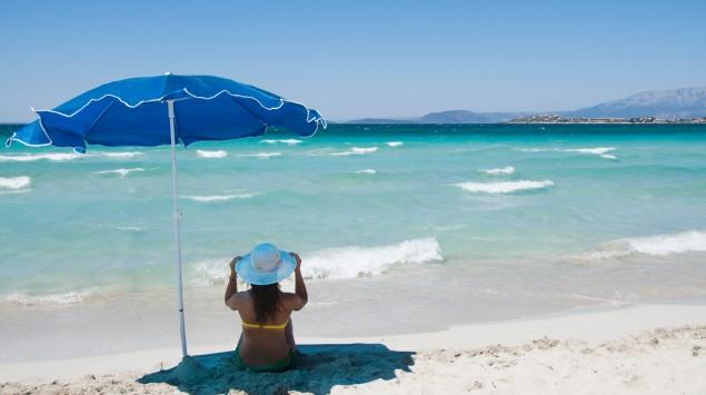 An einem Strand sitzt eine Frau im Schatten eines Sonnenschirms.