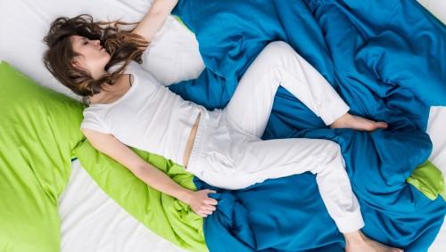 Eine Frau schläft in zerwühlten Laken.