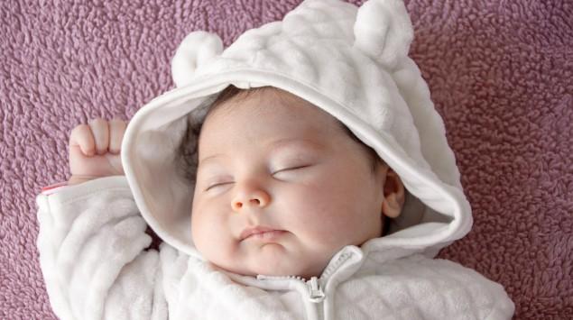 Schlafendes Baby auf lila Decke.
