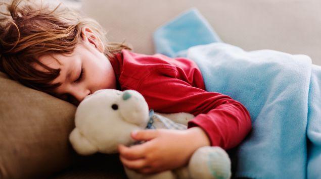 Ein Kind schläft auf einer Couch und hält einen Teddy im Arm.