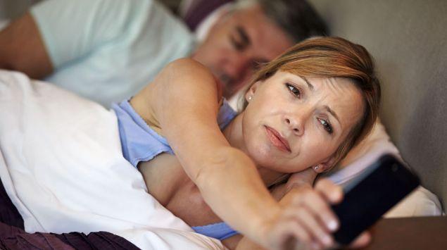 Eine schlaflose Frau blickt auf ihr Smartphone.