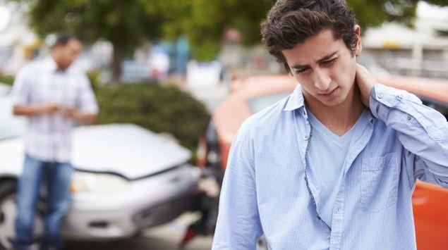 Das Bild zeigt einen junge Mann, der sich nach einem Unfall den Nacken hält.