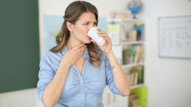 Eine Frau trinkt aus einem Becher und hält sich dabei die freie Hand an den Hals.