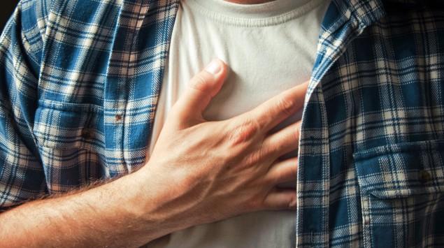 Ein Mann hat die rechte Hand auf die Brust gelegt.