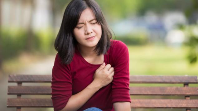 Eine Frau mit Rippenfellentzündung (Pleuritis) hat beim Atmen Schmerzen im Brustkorb.