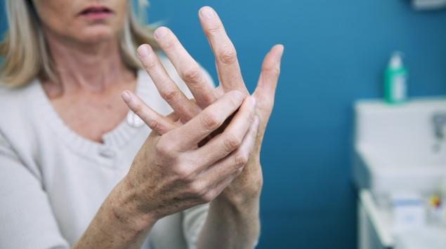 Heberden-Arthrose: Eine Frau umfasst ihre linke mit der rechten Hand.