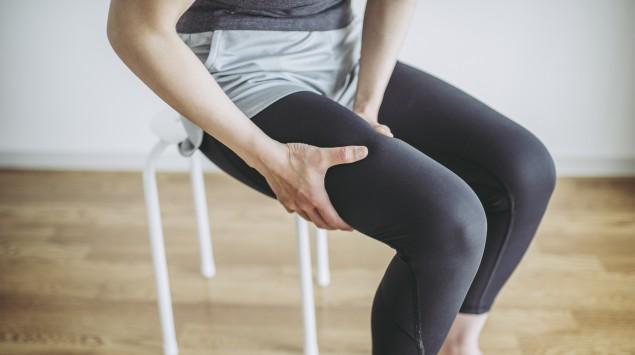 Eine sitzende Frau umfasst ihren rechten Oberschenkel mit den Händen.