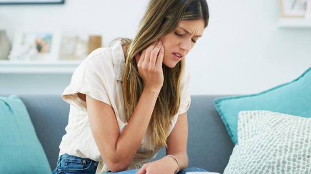 Eine Frau, fasst sich an die schmerzende Wange. CMD-Beschwerden können vielfältig sein.