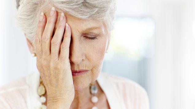 Eine Frau bedeckt die rechte Gesichtshälfte mit ihrer Hand.