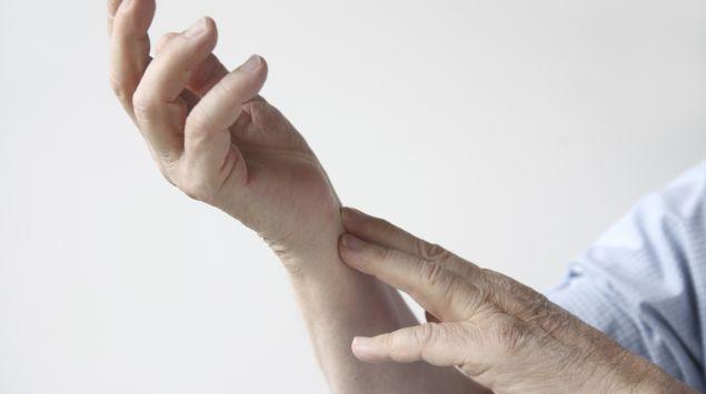 Das Bild zeigt eine Person, die ihr schmerzendes Handgelenk hält.