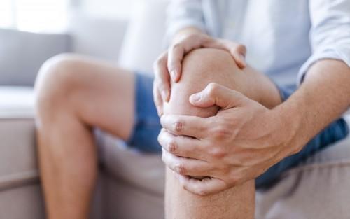 Ein Mann sitzt auf einem Sofa und umfasst das linke Knie mit beiden Händen.