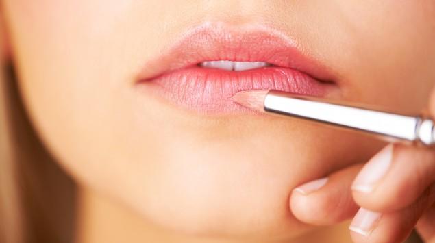 Eine Frau schminkt sich die Lippen.