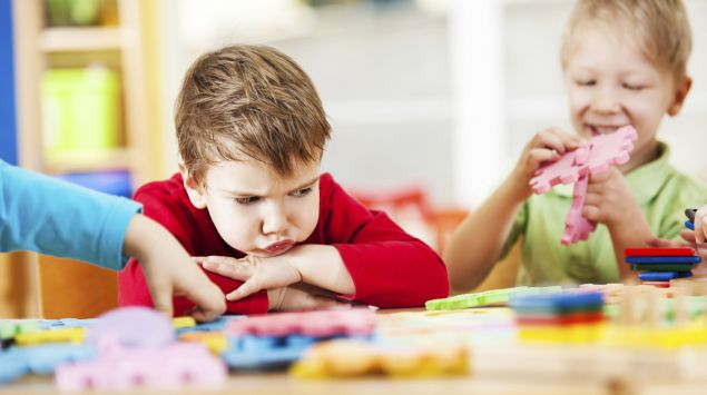 Ein kleiner Junge sitzt mit verschränkten Armen am Tisch und schaut wütend zu einem Puzzle.