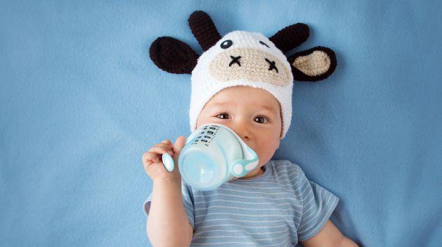 Ein Baby mit Kuhmütze und Schnabeltasse.