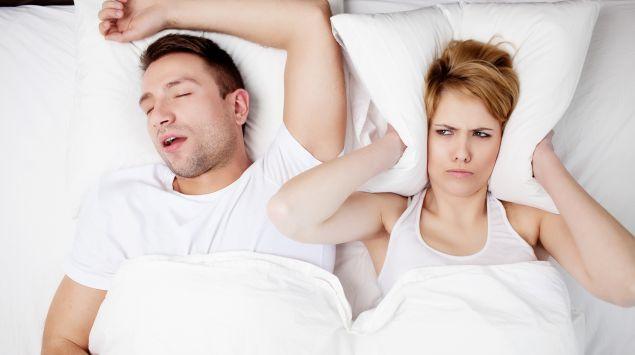 Mann schnarcht, Frau leider darunter im Bett und hält sich die Ohren zu