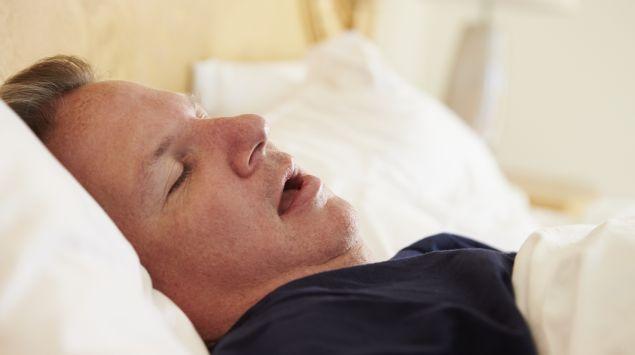 Ein Mann liegt mit offenem Mund im Bett und schnarcht.