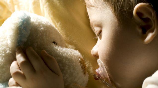 Baby schläft mit Schnuller und Teddy.