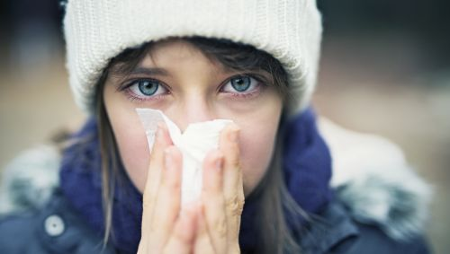 Das Bild zeigt eine junge Frau, die ihre Nase putzt.