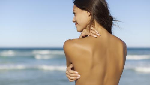 Eine Frau steht mit dem nackten Rücken zu uns am Strand