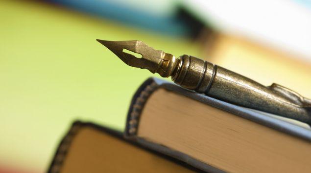 Auf einem Stapel Bücher liegt eine alte Schreibfeder.