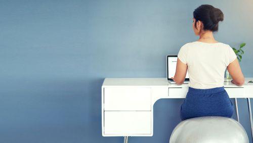 Eine Frau sitzt auf einem Sitzball am Schreibtisch.