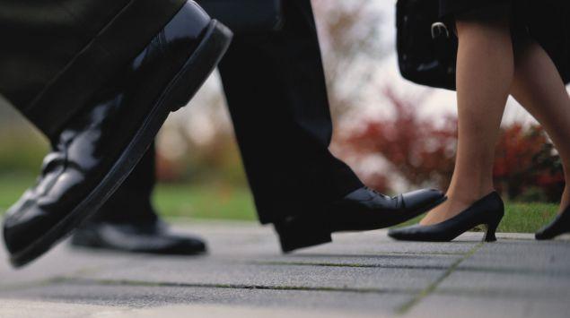 Man sieht die Schuhe von Menschen, die auf der Straße gehen.